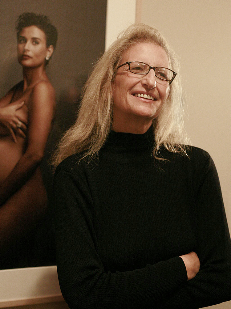 "2008 photograph of Annie Leibovitz in front of her ""More Demi Moore"" photo"