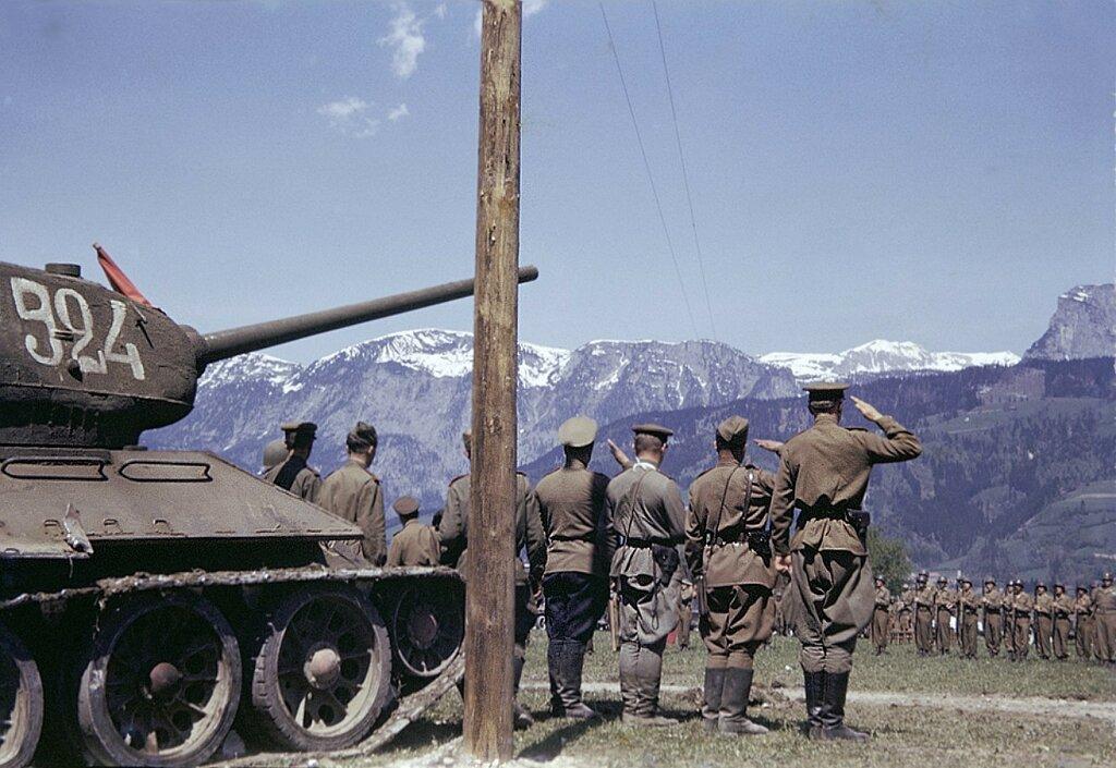 1945_Austria Советские офицеры у танка Т-34-85 салютуют параду 9-й бронетанковой дивизии армии США в районе Линца.jpg