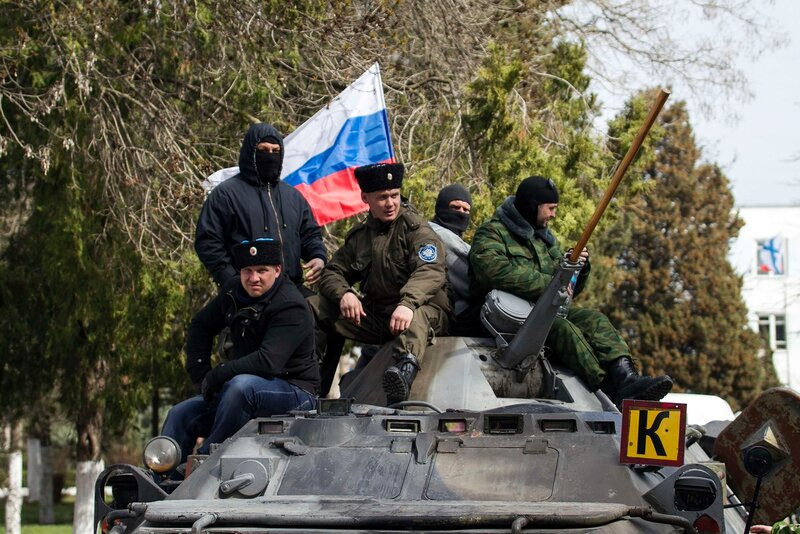 Pro-Russian supporters sit on top of a Ukrainian APC after breaking into the territory of the naval headquarters in Sevastopol