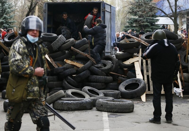 Pro-Russian protestors unload tires to form barricades as an armed man walks past at the police headquarters in Slaviansk