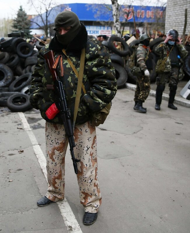 An armed man stands in front of police headquarters in Slaviansk