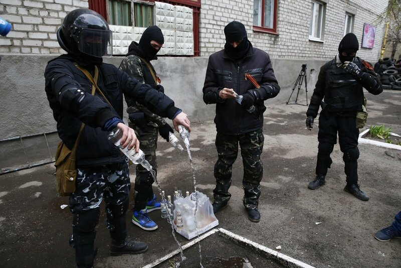 Masked men empty bottles of vodka to use them for petrol bombs in front of police headquarters in Slaviansk