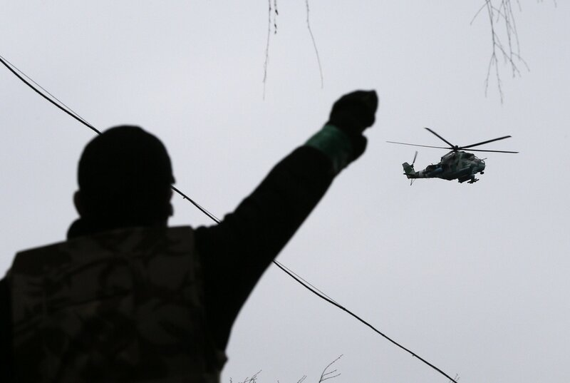 A man gestures while pro-Russian protesters gather at the police headquarters, while a military helicopter flies above, in Slaviansk