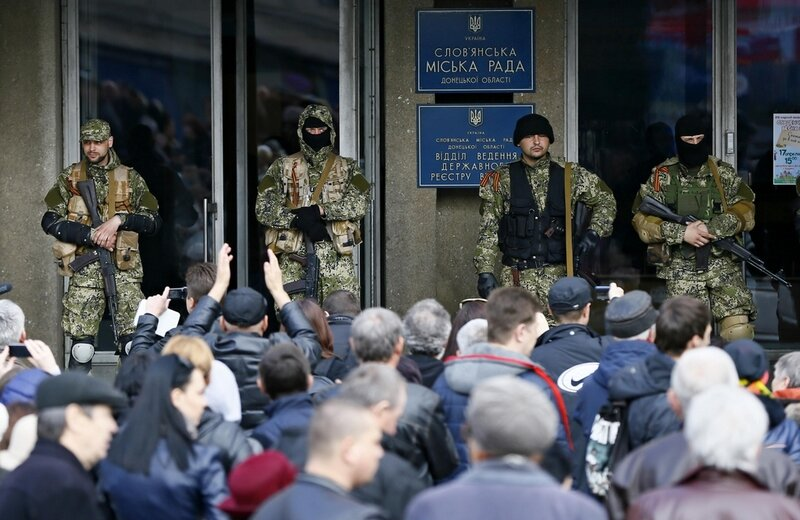 Pro-Russian armed men stand guard as pro-Russian supporters gather outside the mayor's office in Slaviansk