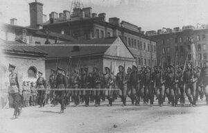 Запасной батальон полка проходит церемониальным маршем мимо начальствующего состава на параде.