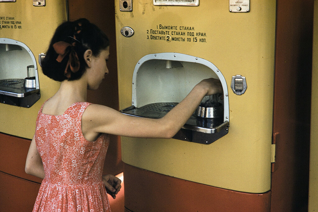 Uzbekistan, girl using soft drink vending machine in Samarkand