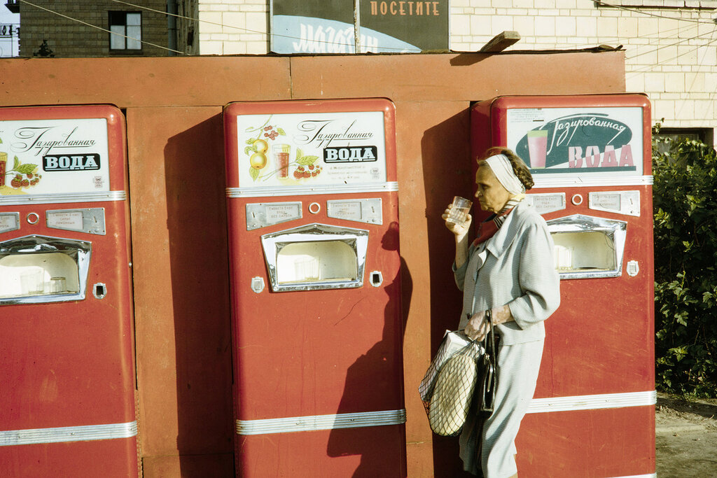 Russia, woman drinking beverage from vending machine in Moscow
