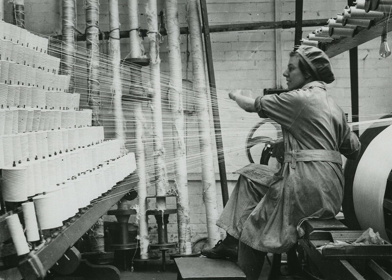 British woman winding cotton from spools on to rollers at lace factory in Nottingham