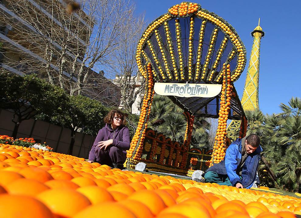 2. Люди работают над скульптурами из апельсинов и лимонов. (Valery Hache, AFP / Getty Images)