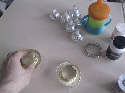 Фото 2. Детали демонтированных светильников (корпуса, пружинные фиксаторы и галогенные 220-вольтные лампы) на кухонном столе.