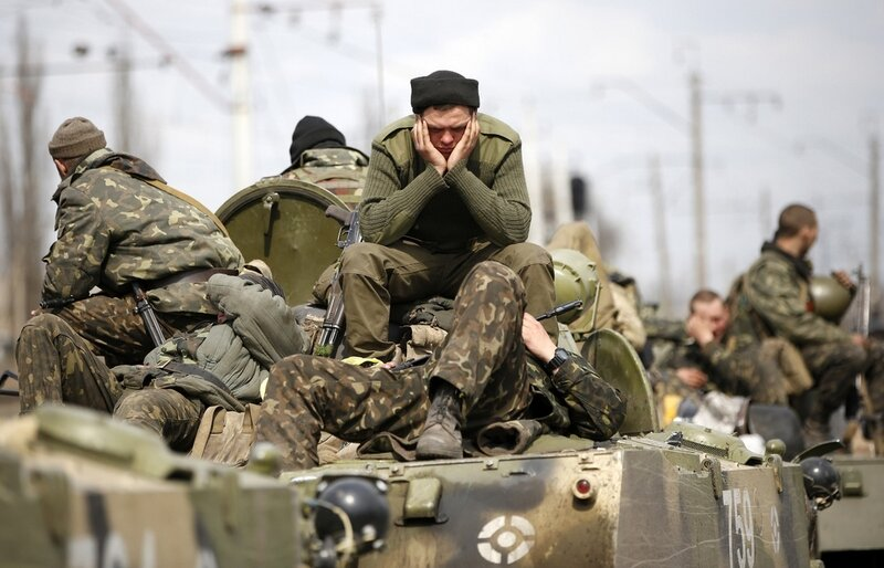 Ukrainian soldiers sit on top of armoured personnel carriers in Kramatorsk