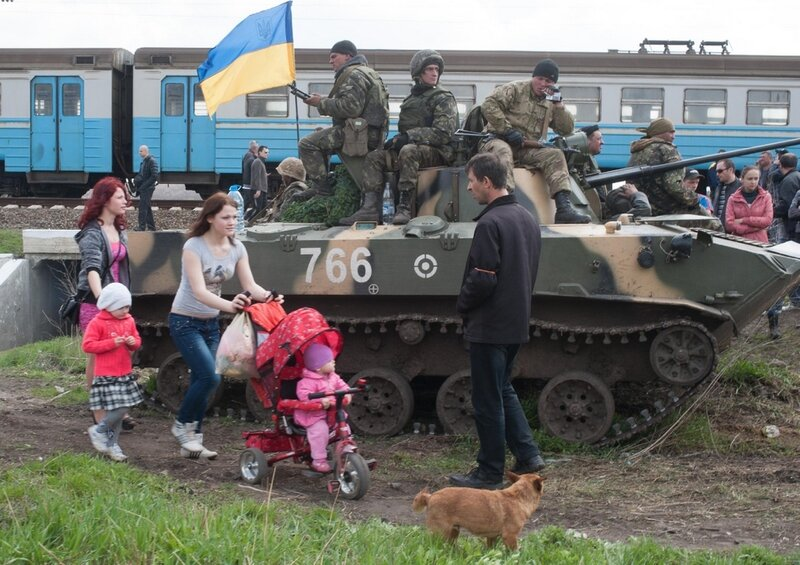 People walk past an Ukrainian Army combat vehicle parked near a railway in Kramatorsk, Ukraine, Wednesday, April 16, 2014. The central government has so far been unable to rein in the insurgents, who it says are being stirred up by paid operatives from Ru
