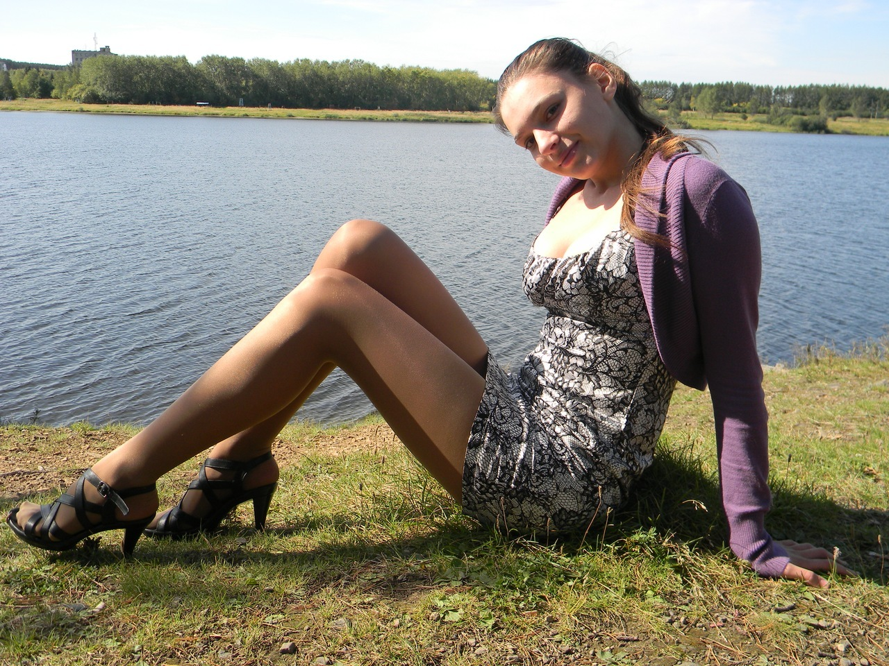 Симпатичная девушка на берегу озера в колготках