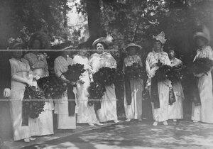 Жены офицеров Конно-гренадерского полка готовятся к возложению цветов у подножия памятника шефу полка , великому князю Михаилу Николаевичу в день его открытия  .