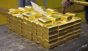 An employee transports pre-cast bars of gold in a box at a plant of refiner and bar manufacturer Argor-Heraeus SA in the southern Swiss town of Mendrisio
