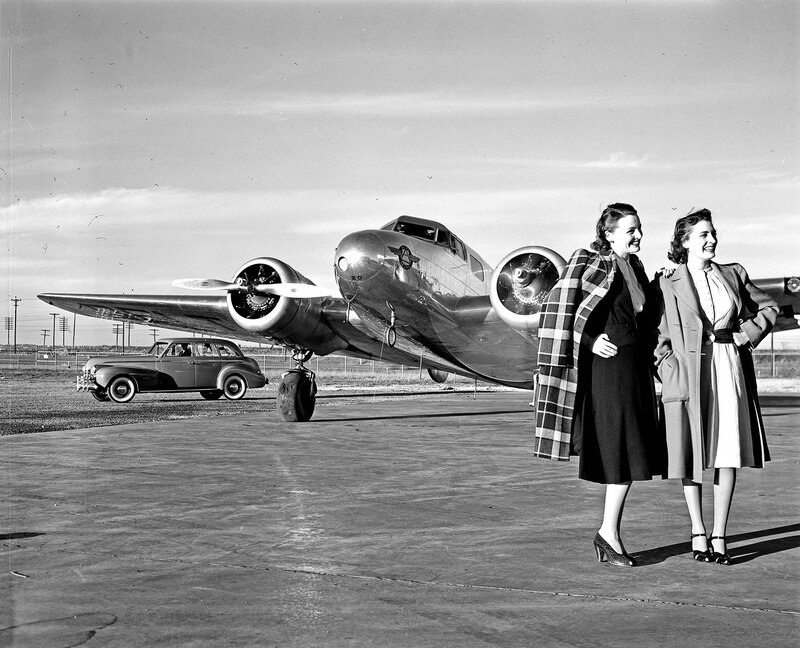 Two models standing in front of a Lockheed Model 10B Electra, owned by Delta Air Lines, at Dallas Love Field Airport. Behind the aircraft is an Oldsmobile Series 70 automobile. March 1940