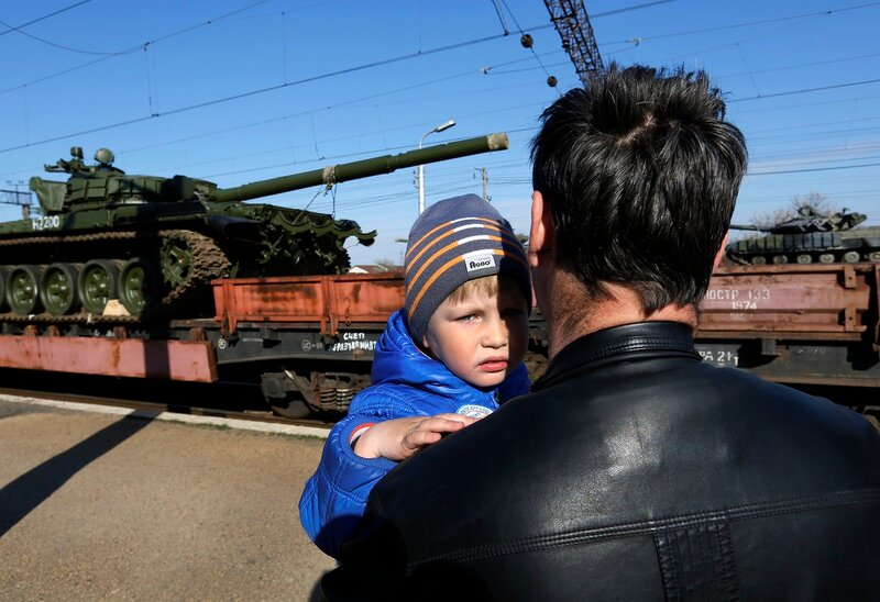 A father and son watch Russian tanks arriving onboard a train in the Crimean settlement of Gvardeiskoye near the city of Simferopol