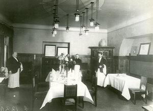 Официанты у стола, накрытого на восемь человек.