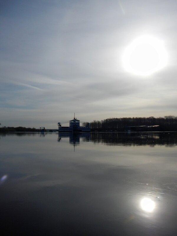 Солнце отражается в воде разлившейся Вятки в районе городского пляжа и Титаника