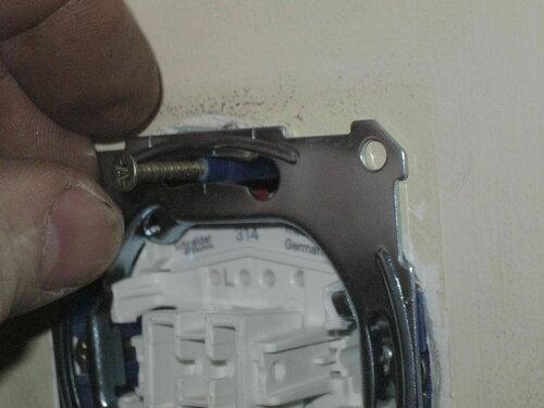 Фото 32. Уплотнитель с саморезом вставлен в отверстие установочной коробки.