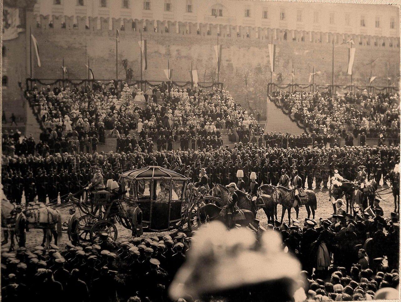 Коронационная карета императрицы Александры Федоровны проезжает мимо трибун со зрителями у Кремлевской стены на Красной площади в день торжественного въезда их императорских величеств в Москву