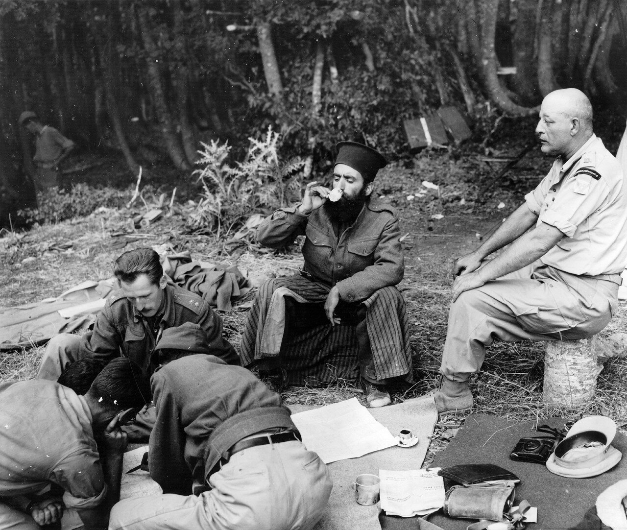 1947. Офицеры планируют нападение, в то время как священник пьет кофе. В каждой бригаде был священник, который ехал вместе с ними