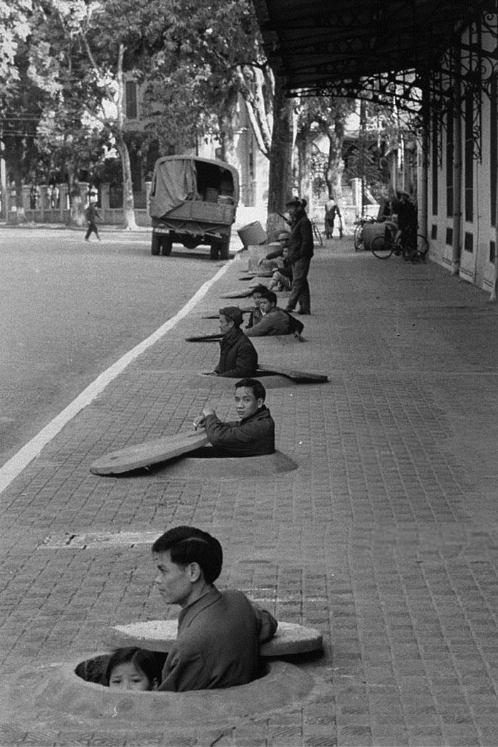 Жители Ханоя ждут сигнала отбоя воздушной тревоги во время воздушного налета