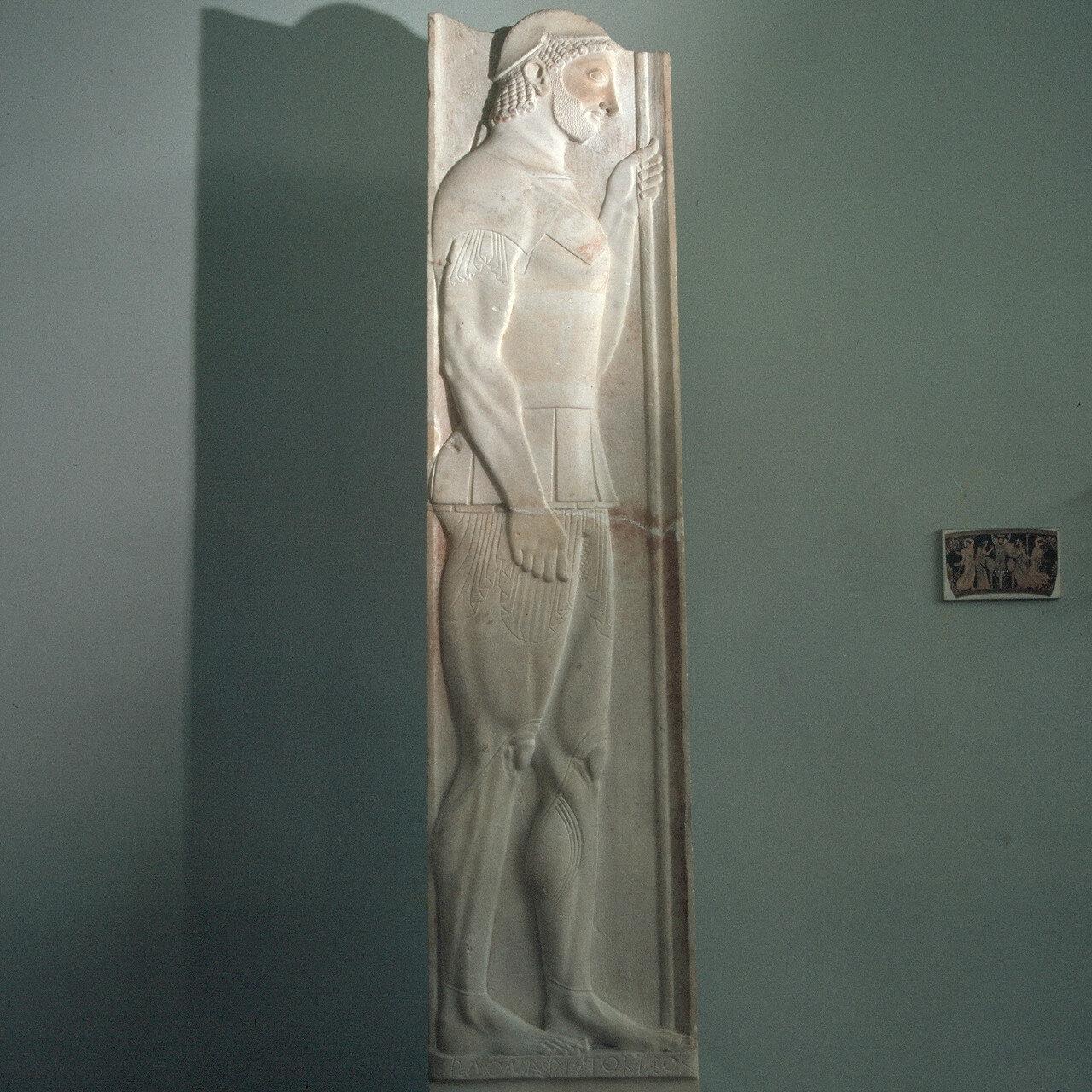 Стела Аристиона. Архаический гоплит в хитоне, шлеме, доспехах и с копьем. Мрамор. Конец VI в. до н. э.