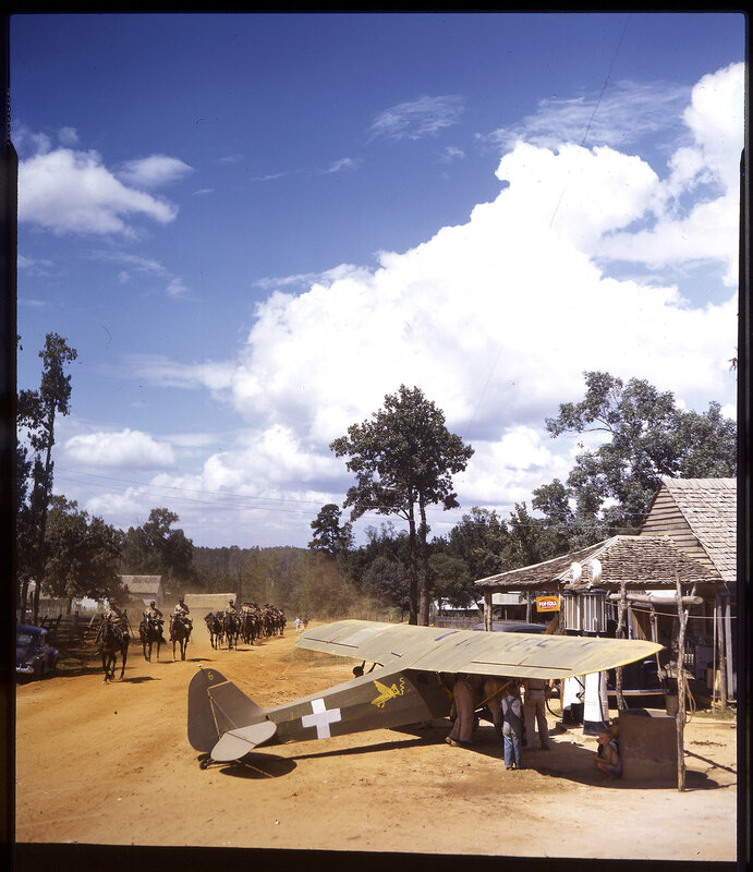 One-half right rear view of Piper J-3C Cub (NX38505; a/c N? 6) parked at a store/filling station in Louisiana during the 1941 Louisiana Maneuvers.  A cavalry unit is shown passing by the J-3.  Aircraft has a white cross painted on the side of the fuselage