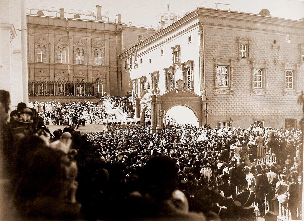 Зрители на трибуне у Большого Кремлевского дворца, горожане и нижние чины шефских частей на Соборной площади наблюдают торжественное шествие императора Николая II (под балдахином) в сопровождении свиты