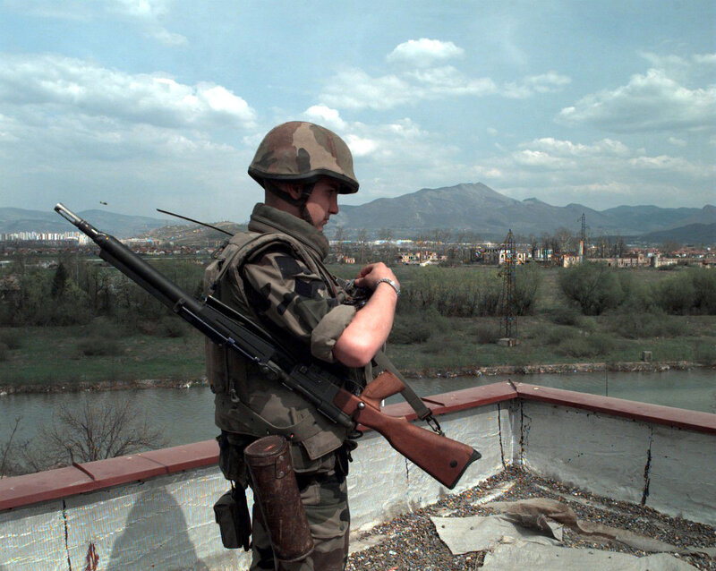 French Army Private First Class Yannick Chevalier, armed with a French sniping rifle, stands guard atop the Terme Hotel at the Allied Command Europe Rapid Reaction Corps Headquarters located in the Sarajevo suburb of Ilidza, Bosnia-Herzegovina.