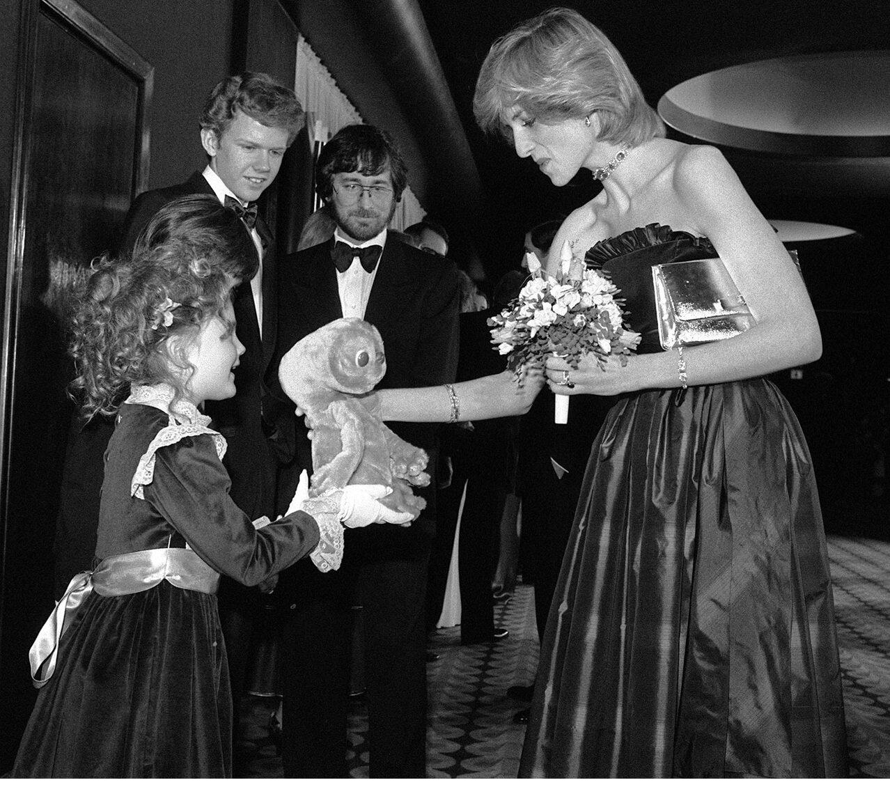 1982.. Дрю Бэрримор дарит принцессе Диане куклу «Ити», в момент когда она вместе с Робертом МакНотоном и Стивеном Спилбергом находилась на Лондонской премьере «Инопланетянина»