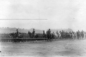 Император Николай II и сопровождающие его лица объезжают войска перед началом парада.