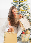 Smiling young woman with shopping bags near christmas tree