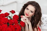 Attractive smiling girl with bouquet of red roses at modern inte