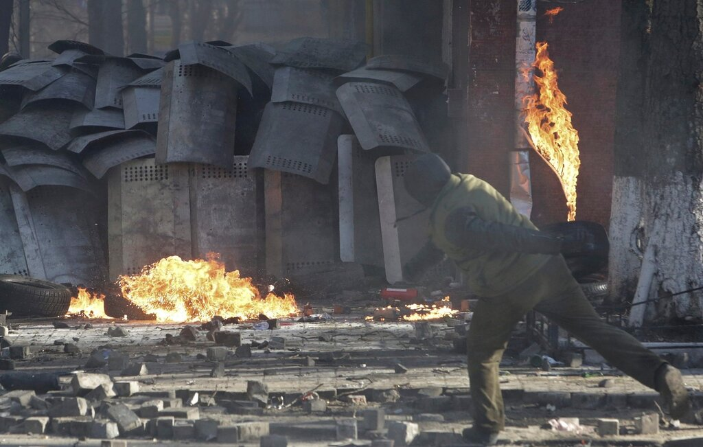 A protester throws a petrol bomb towards Interior ministry members during clashes in Kiev