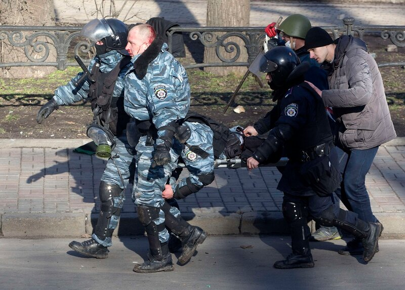 Riot police officers carry their colleague who was injured during clashes with anti-government protesters in Kiev