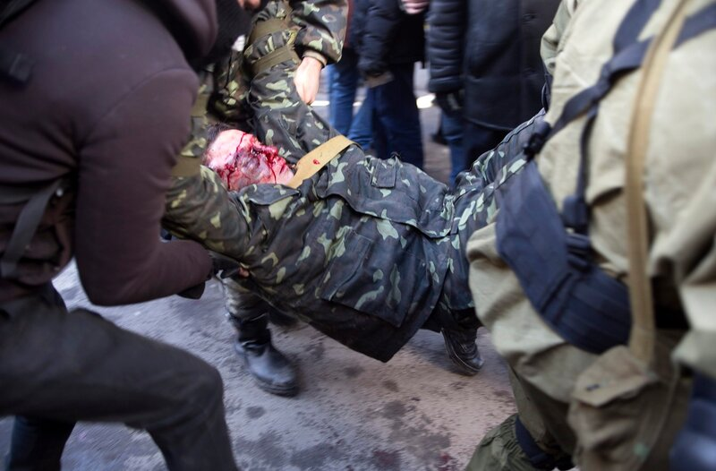 An anti-government protester who was injured during clashes with Interior Ministry members is transported on a stretcher in Kiev