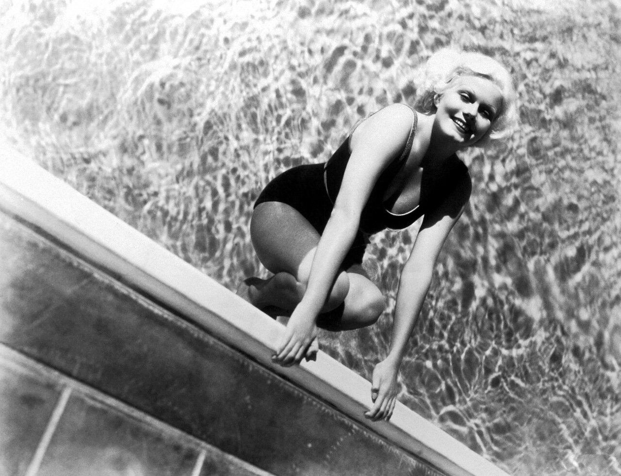 1935: Portrait of American actor Jean Harlow (1911 - 1937) smiling as she holds on to the side of a swimming pool. She wears a bathing suit.