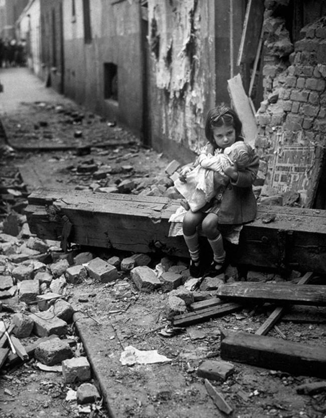 Девочка скуклой сидит около своего разрушенного после бомбежки дома, 1940г.