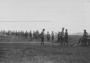 Группа солдат в поле у орудия.