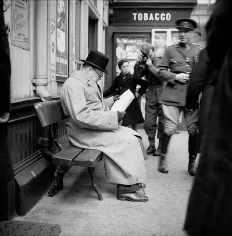 1940. Премьер-министр Уинстон Черчилль читает газету на платформе в ожидании поезда в Сент-Эндрюс во время поездки в Шотландию 23 октября