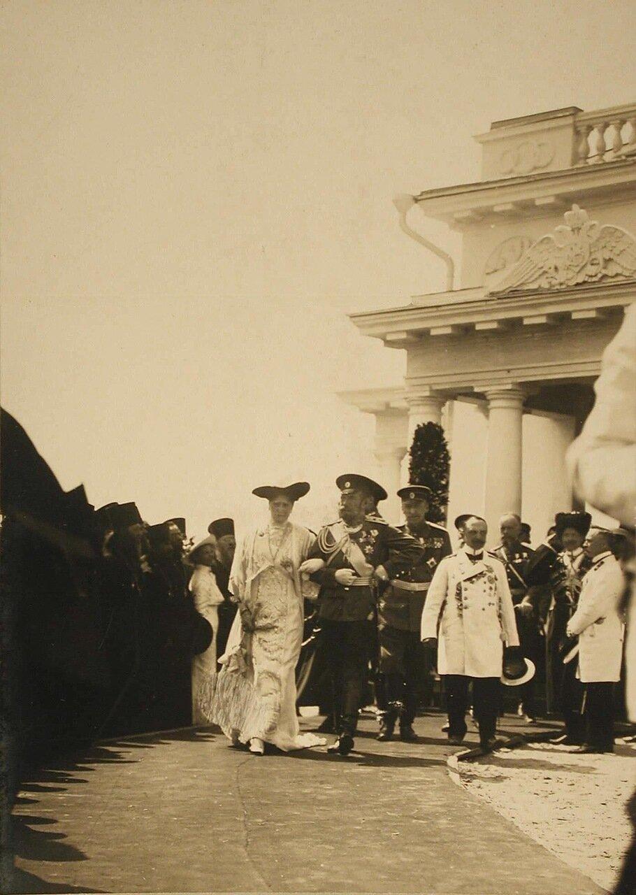 07. Император Николай II, императрица Александра Федоровна проходят мимо группы священнослужителей после окончания церемонии закладки памятника 300-летия царствования дома Романовых