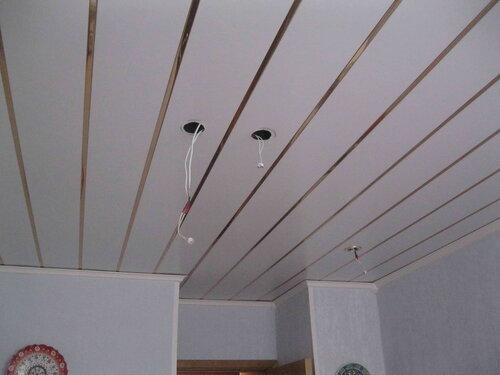 Фото 3. Подвесной реечный потолок кухни. Общий вид. Через отверстия, предназначенные для установки светильников, производится осмотр проводки, скрытой от взора алюминиевыми рейками потолка.