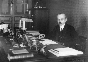 Управляющий банком Ал. Вл. Коншин за столом в кабинете.