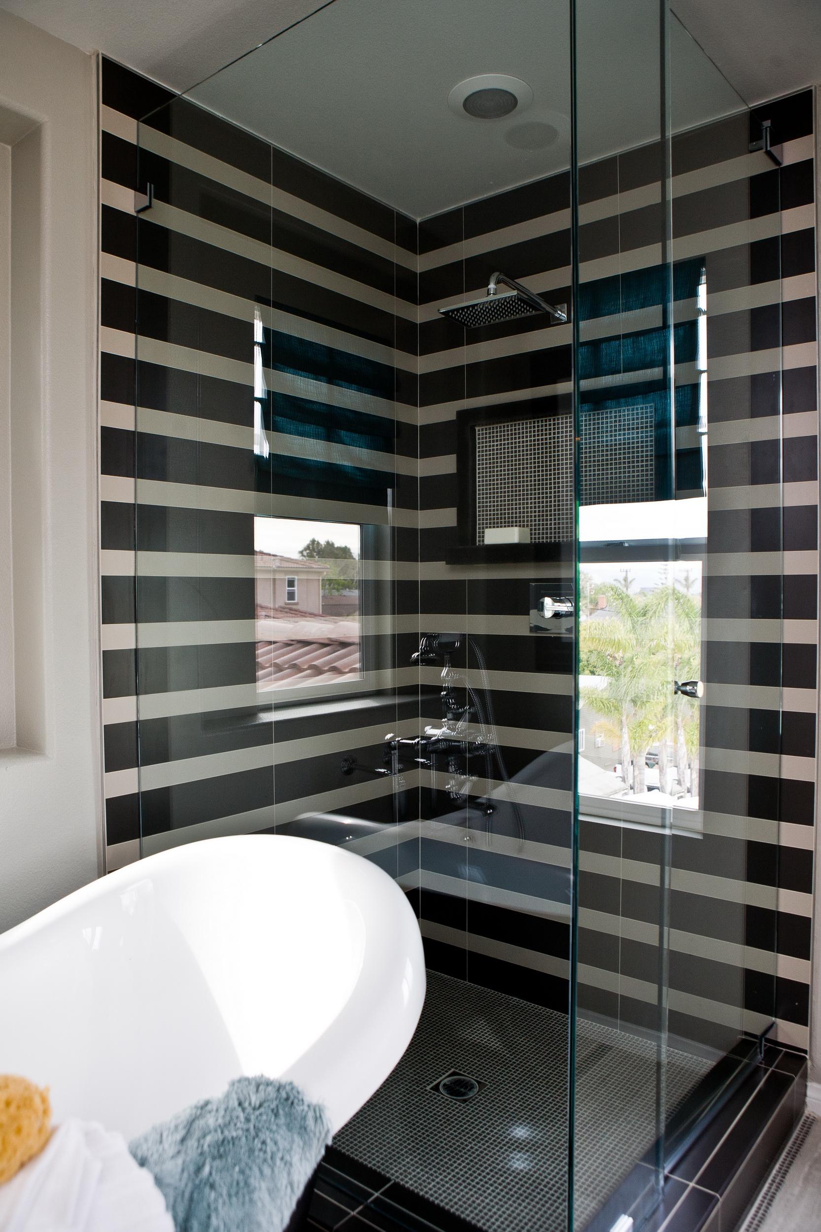 Интерьер ванной комнаты. Стеклянные стенки душевой кабины. Черные полоски на стенах.