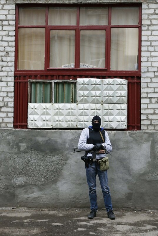 An armed man stands in front of the police headquarters in Slaviansk