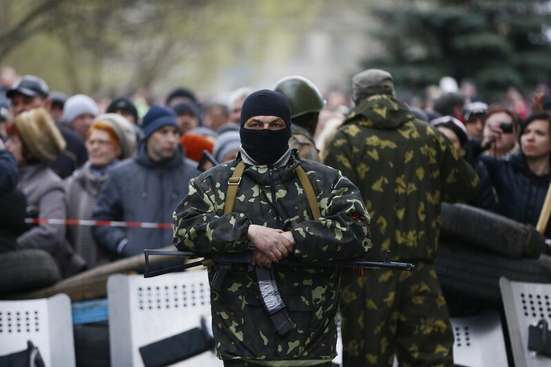 An armed man stands in front of pro-Russian protesters near the police headquarters in Slaviansk