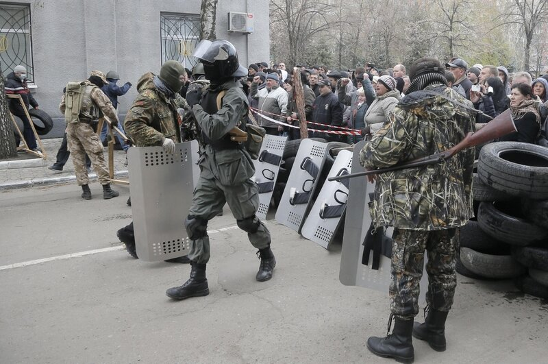 Armed pro-Russian activists occupy the police station carrying riot shields as people watch on, in the eastern Ukraine town of Slovyansk on Saturday, April 12, 2014. Pro-Moscow protesters have seized a number of government buildings in the east over the p