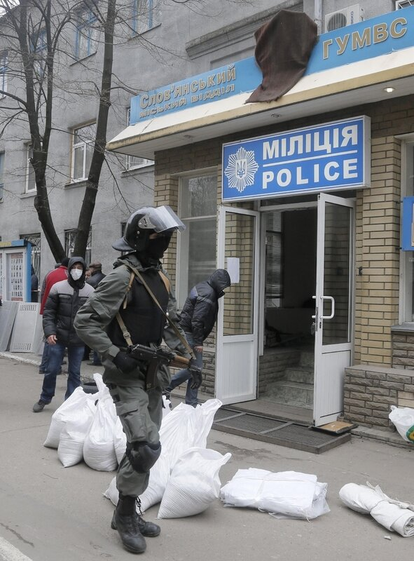 Armed pro-Russian activists occupy the police station carrying riot shields in the eastern Ukraine town of Slovyansk on Saturday, April 12, 2014. Pro-Moscow protesters have seized a number of government buildings in the east over the past week, underminin